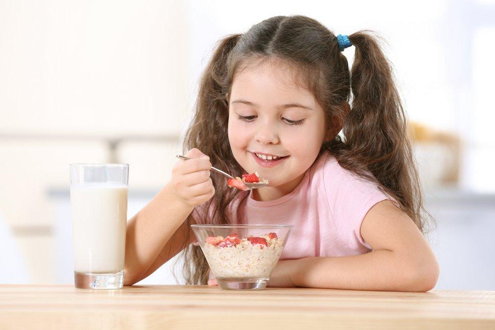 Девочка ест овсянку с ягодами на завтрак